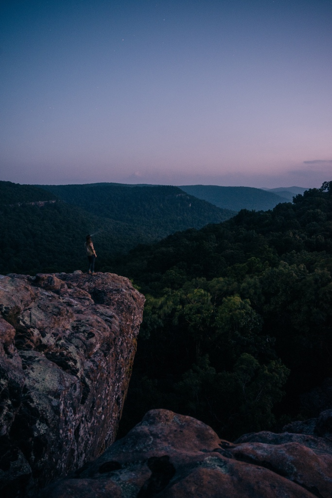 Girl with a headlamp on a rocky outcropping at night