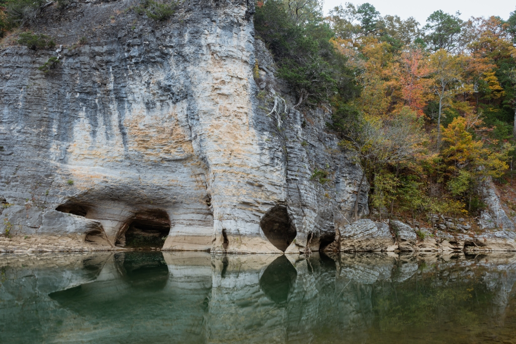 A bluff with interesting formations reflected in a river