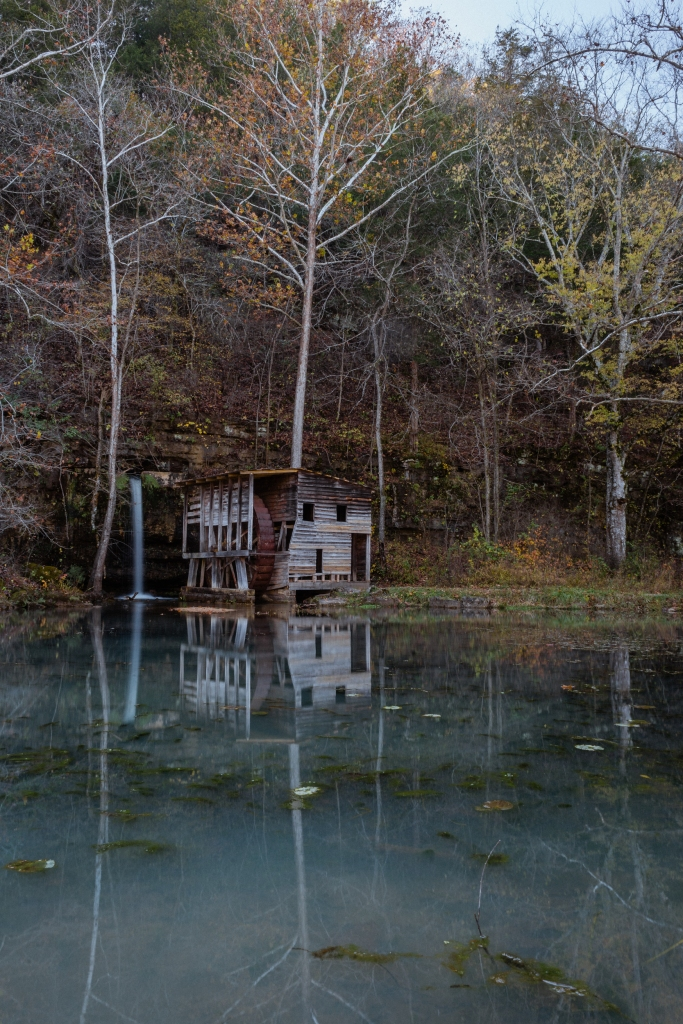 Old mill and waterfall reflected in a green pool