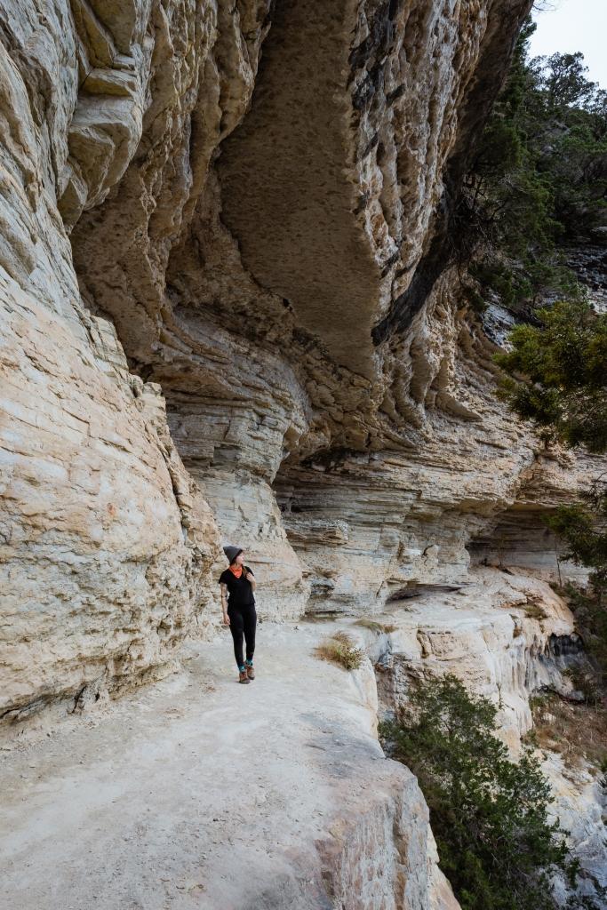 A hiker walks along a narrow bluff