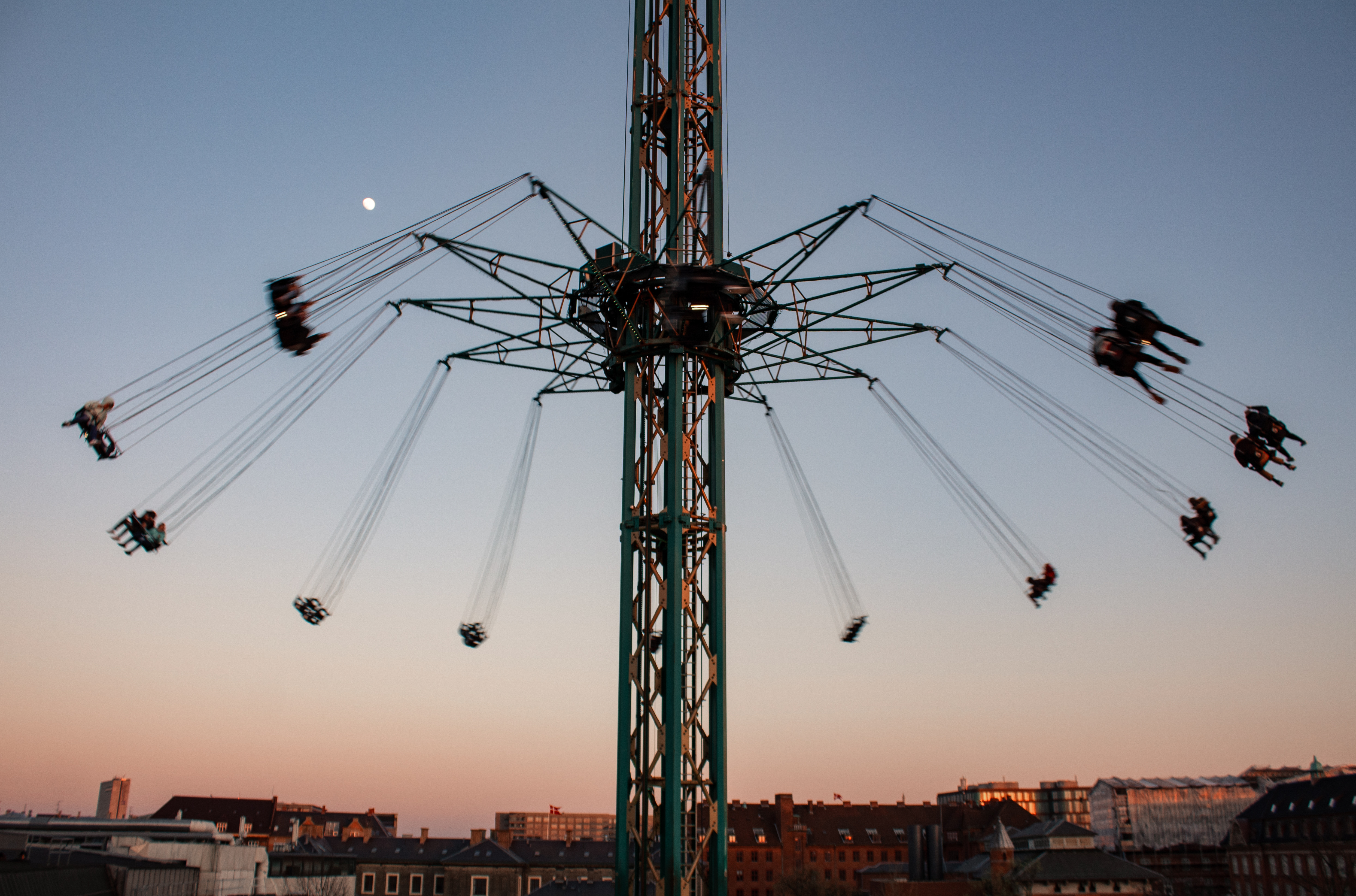 Moon and amusement park ride in Copenhagen at dusk, city architecture
