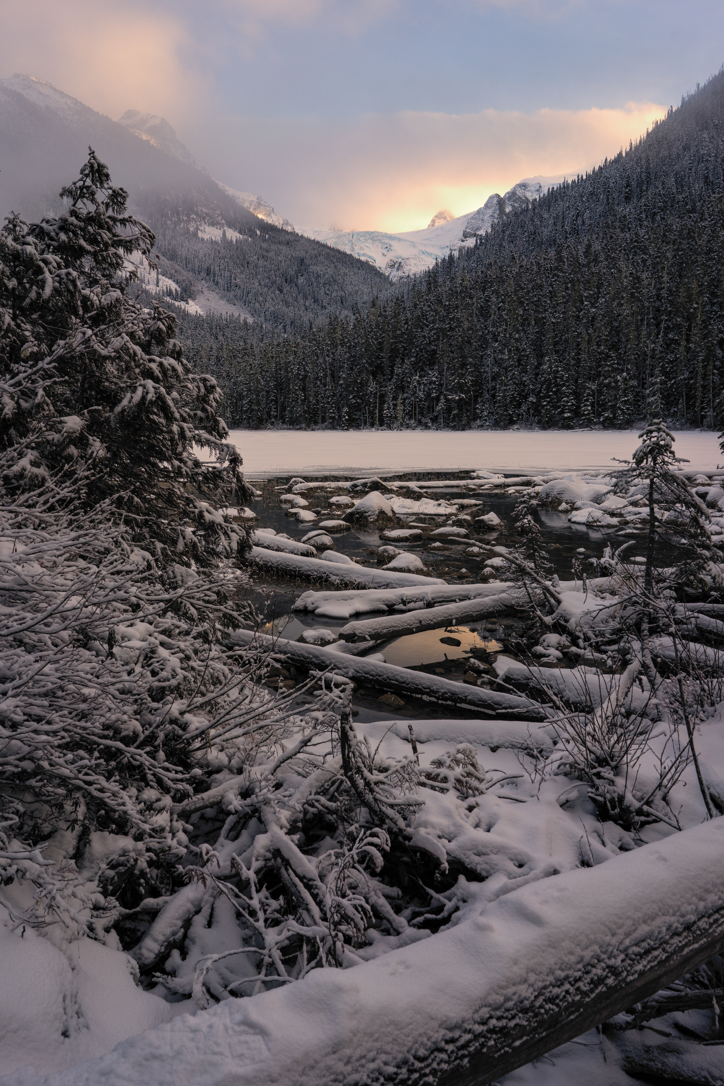 Foggy golden light on a snowy mountains scene and lake