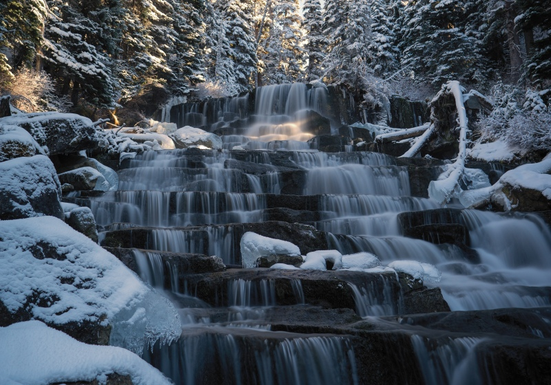 Snowy waterfall glowing in the afternoon light