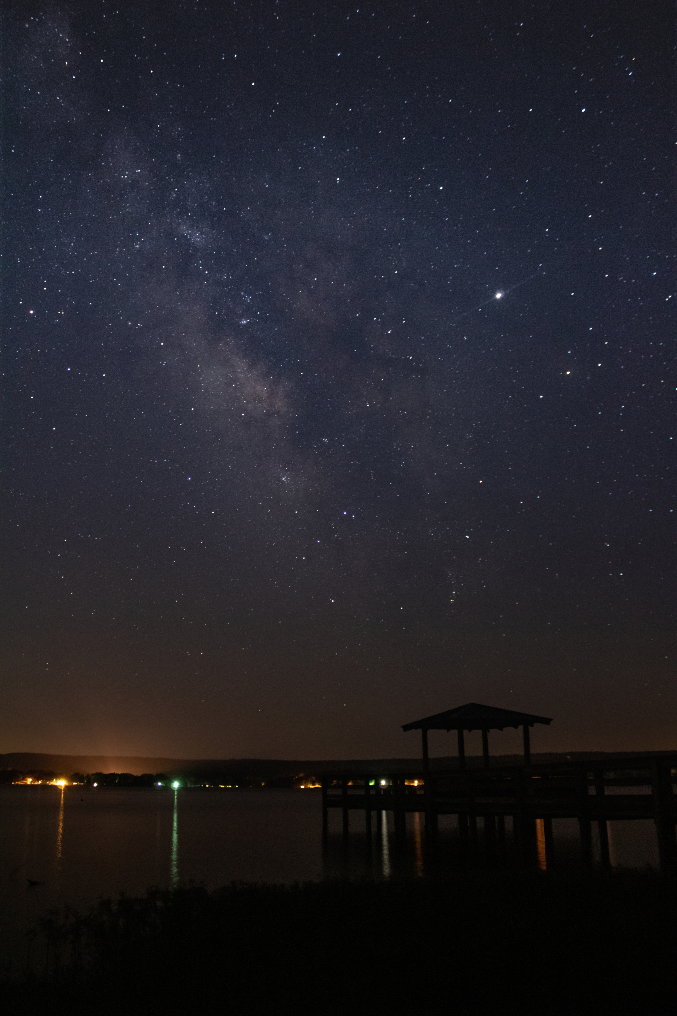 Milky Way night sky over pier and lake
