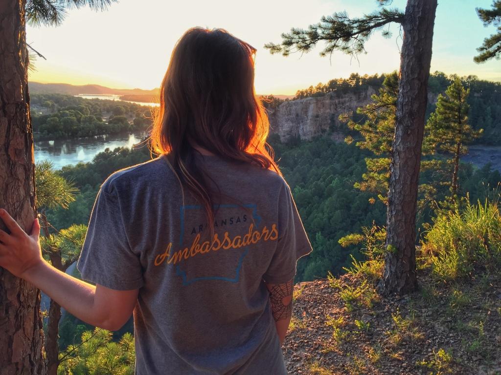 Back of girl wearing Arkansas Ambassadors t-shirt at sunset at Emerald park