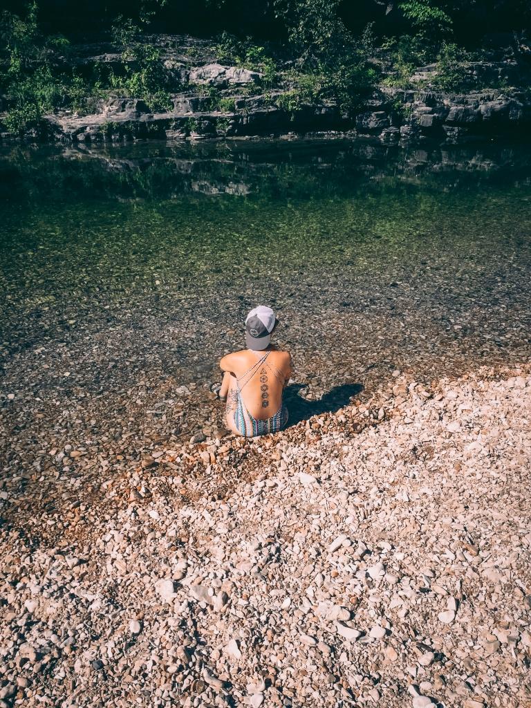 Tattooed girl sitting in an Arkansas creek at Blanchard Springs
