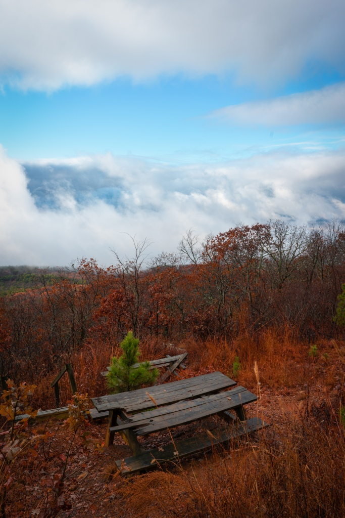 Old picnic table on a mountain looking over clouds