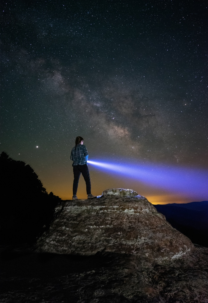 Girl shining a flashlight on a rock in front of the Milky Way