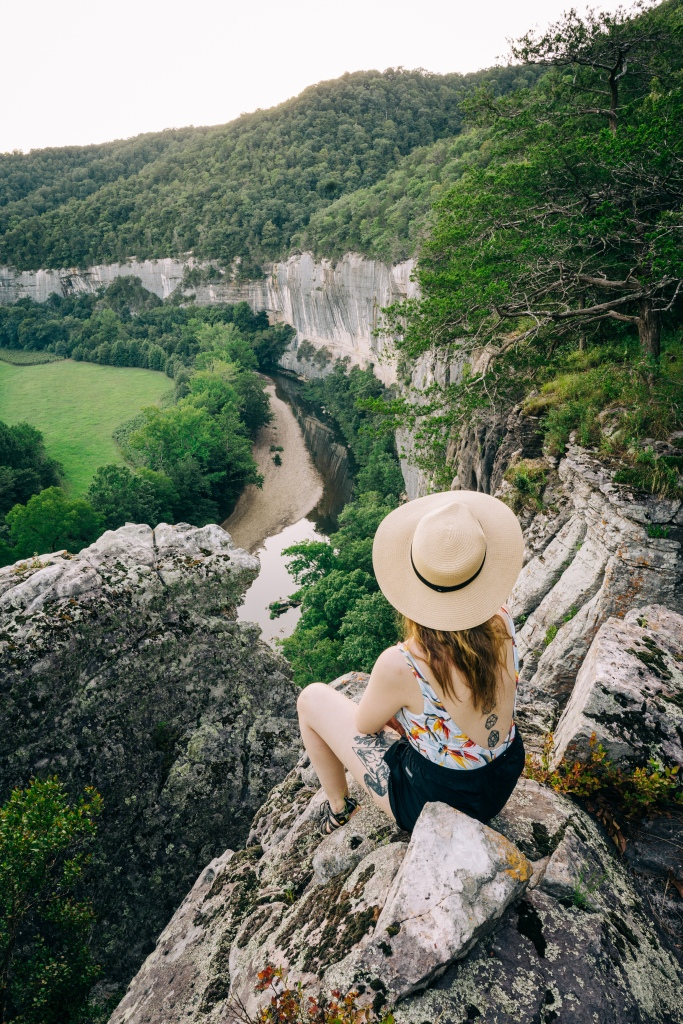 Girl in hat sitting at an overlook at Buffalo National River