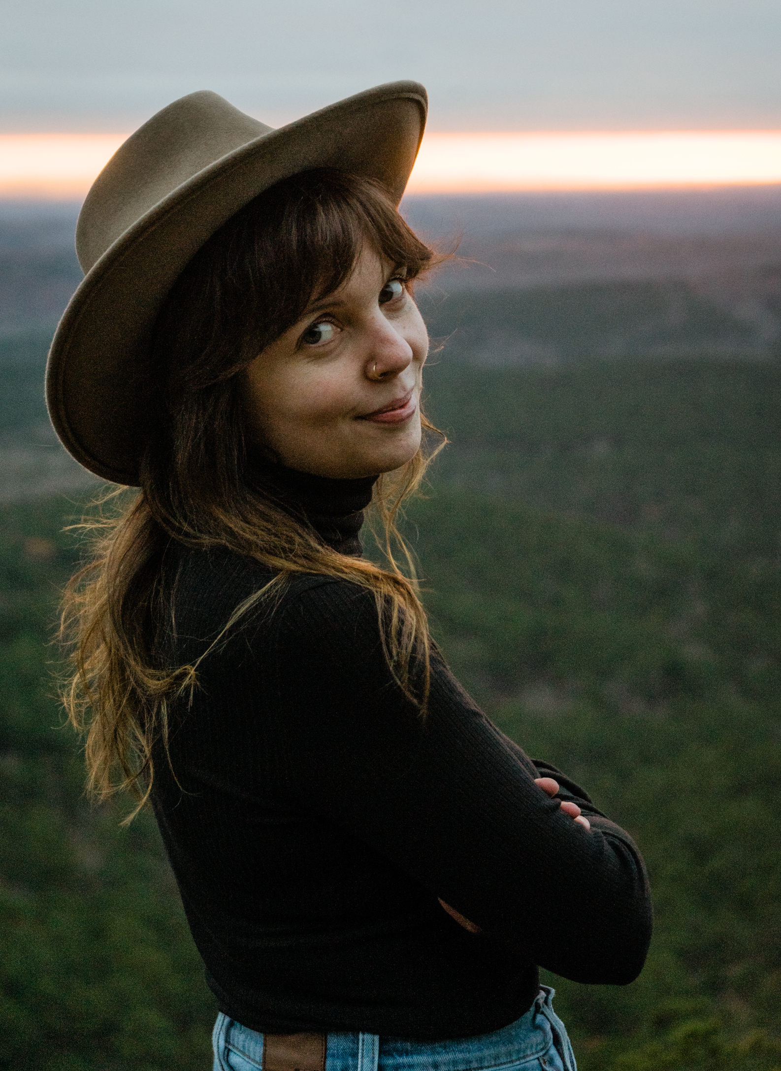 A woman in a cowboy hat with folded arms smiling and looking back at the camera