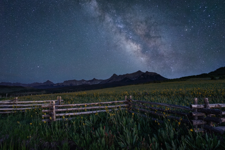 Milky Way over fence and mountains on the Last Dollar Road