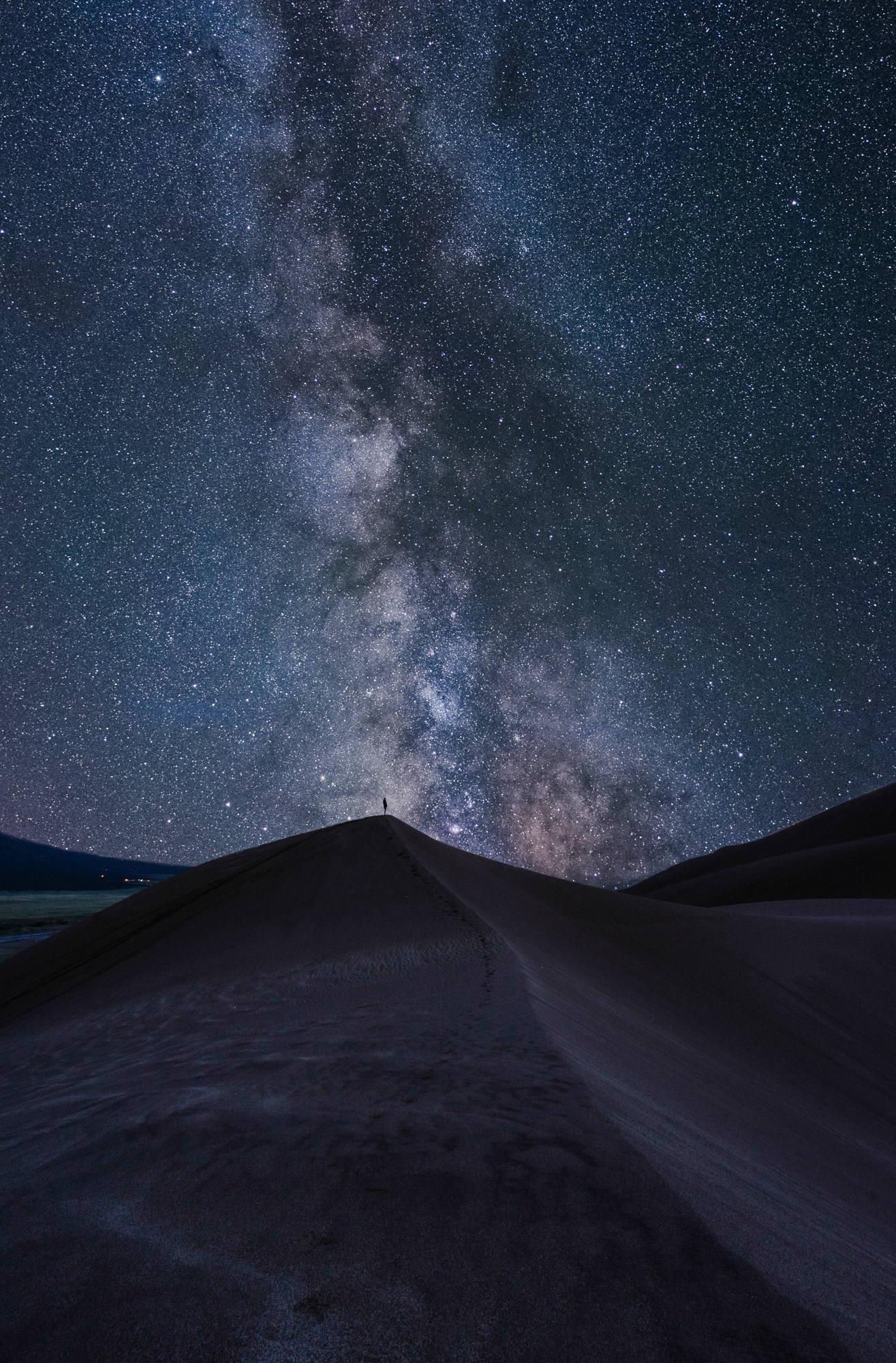 Milky Way over small figure standing on a sand dune
