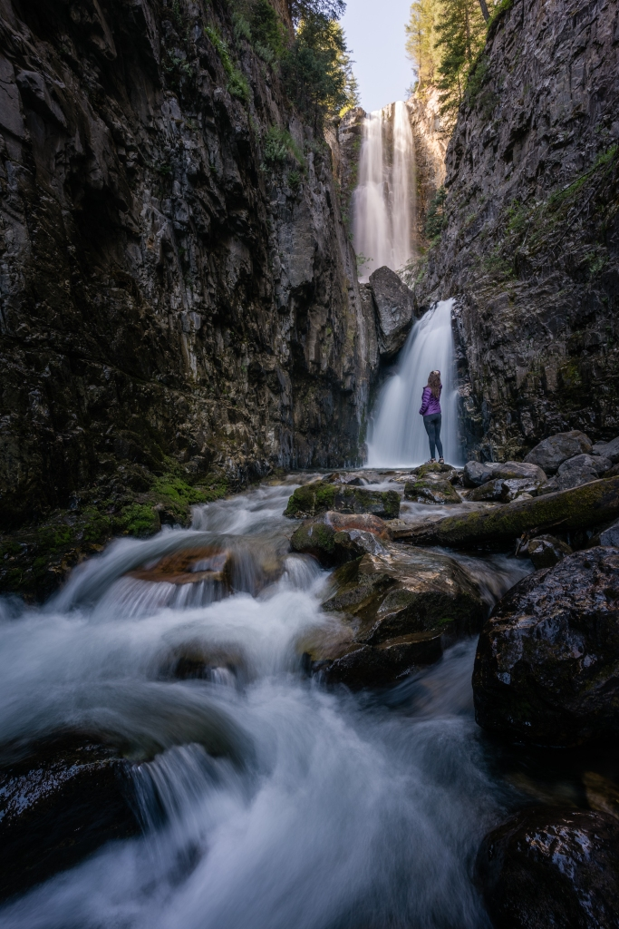 A woman standing in front of a tall rushing waterfall