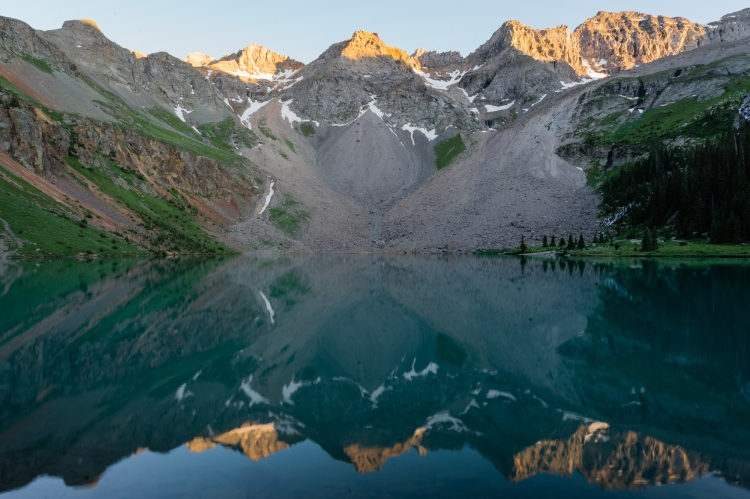Sunset on mountain peaks reflected in a blue lake