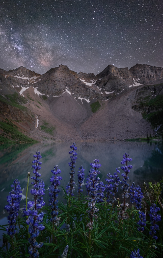 Milky Way over purple lupines and lake in the San Juan mountains