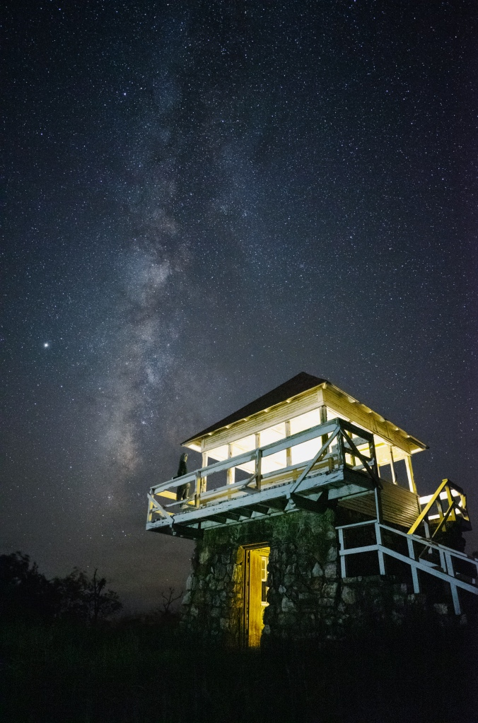 Girl looking at the Milky Way from an old fire tower