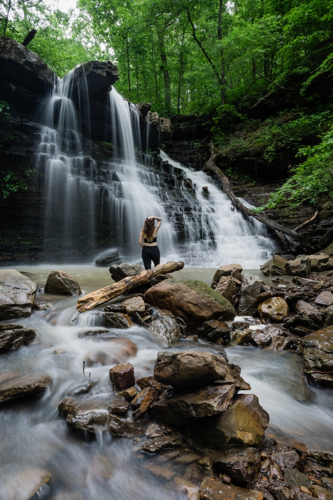 Woman stands at the base of a big waterfall in a green lush forest